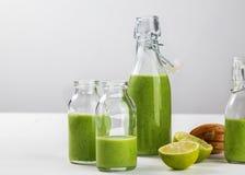 新鲜的做的健康绿色圆滑的人在白色背景的瓶服务 水果和蔬菜和种子成份 关闭 图库摄影