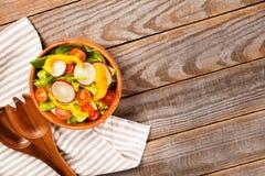 新鲜的健康沙拉用莴苣,蕃茄,胡椒,在木背景的萝卜 免版税库存照片
