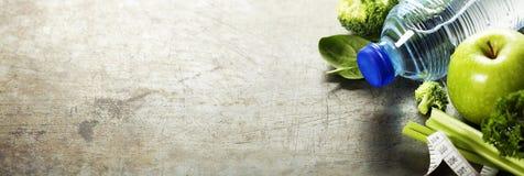 新鲜的健康菜、水和测量的磁带 免版税库存图片