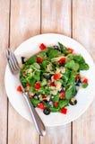 新鲜的健康素食主义者沙拉用奎奴亚藜,菜用结页草、黑橄榄、红辣椒和橄榄油在白色板材布料在白色木bac 免版税库存图片