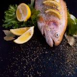 新鲜的准备在黑桌上的鱼宴的鳟鱼和成份,用香料和柠檬,顶视图 免版税库存图片