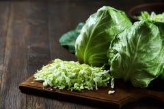 新鲜的切的圆白菜的特写镜头在一个木板的在木背景 免版税库存照片