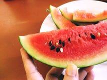 新鲜的切的西瓜在手中 免版税库存照片