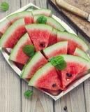 新鲜的切的西瓜在金属碗木背景中 免版税库存照片