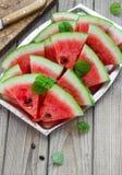 新鲜的切的西瓜在金属碗木背景中 图库摄影