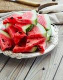 新鲜的切的西瓜在金属碗木背景中 免版税库存图片