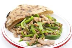 新鲜的切的辣椒的果实用切的鸡肉和平的面包 免版税库存图片