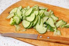 新鲜的切的黄瓜和刀子在木切板 库存照片
