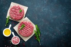 新鲜的剁碎的牛肉肉汉堡用在黑暗的背景的香料 未加工的绞细牛肉肉 免版税库存照片