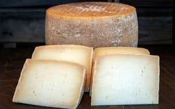 新鲜的可口健康乳酪轮子,有在前景的四个乳酪切片的 免版税库存照片
