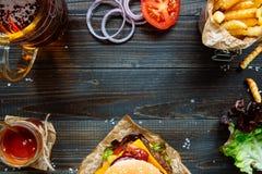 新鲜的可口汉堡用炸薯条、调味汁和啤酒在木台式视图 库存图片