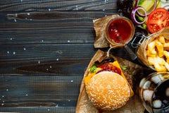 新鲜的可口汉堡用炸薯条、调味汁和饮料在木台式视图,与拷贝空间 免版税图库摄影