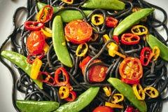 新鲜的可口黑素食主义者意粉用蕃茄,辣椒,在一块白色板材 库存图片