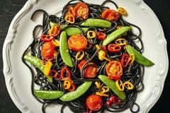 新鲜的可口黑素食主义者意粉用蕃茄,辣椒,在一块白色板材 免版税库存图片