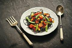 新鲜的可口黑素食主义者意粉用蕃茄,辣椒,在一块白色板材 库存照片