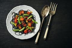 新鲜的可口黑素食主义者意粉用蕃茄,辣椒,在一块白色板材 免版税库存照片