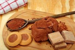 新鲜的可可粉、木匙子和蛋糕 免版税图库摄影