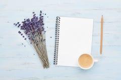 新鲜的咖啡、干净的笔记本和淡紫色在蓝色背景从上面开花 妇女运转的书桌 舒适早餐舱内甲板位置 免版税图库摄影