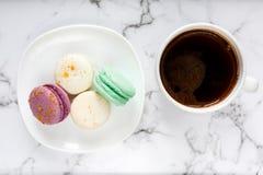 新鲜的咖啡杯和板材有五颜六色的macarons的在大理石桌背景 可口咖啡休息 库存照片