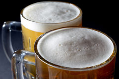 新鲜的啤酒特写镜头与泡沫的在黑背景的两个啤酒杯 库存照片