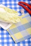 新鲜的圆白菜和红辣椒在白色板材 库存照片
