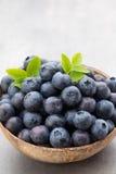 新鲜的在一个碗的蓝莓自然椰子在灰色背景 库存图片