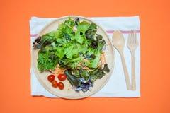 新鲜的在橙色背景顶视图的沙拉用果子和绿色 健康的食物 吃干净的概念 平的位置 免版税库存图片
