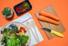 新鲜的在橙色背景顶视图的沙拉用果子和绿色 健康的食物 吃干净的概念 平的位置 免版税库存照片