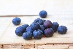 新鲜的地方在土气木背景的蓝莓宏观射击 免版税库存照片
