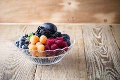 新鲜的夏天莓果和果子在玻璃碗在木土气 免版税库存照片