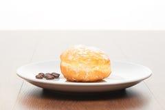新鲜的多福饼用糖粉和咖啡豆在白色陶瓷板材在明亮的浅褐色的木桌上 免版税库存照片