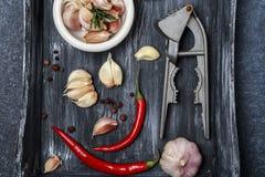 新鲜的大蒜用在黑暗的背景的辣椒 电灯泡新鲜的大蒜朝向三 免版税库存图片
