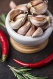 新鲜的大蒜用在黑暗的背景的辣椒 电灯泡新鲜的大蒜朝向三 免版税库存照片