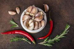 新鲜的大蒜用在黑暗的背景的辣椒 电灯泡新鲜的大蒜朝向三 免版税图库摄影