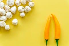新鲜的大蒜隔绝了和在黄色背景的辣椒粉,空的空间 免版税库存图片