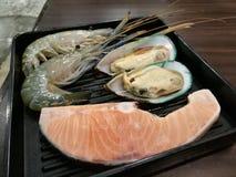 新鲜的大虾、淡菜和三文鱼在冰和超级市场有迷离背景,生气勃勃日本海鲜肉BBQ的, focu 免版税库存照片