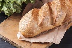 新鲜的大面包洒与在一张木桌上的芝麻 可口烘烤 库存照片