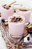 新鲜的奶昔,酸奶,点心,圆滑的人用装饰的草莓磨碎了巧克力和冷冻蓝莓 免版税图库摄影