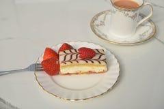新鲜的奶油色切片蛋糕用草莓和茶 免版税库存图片