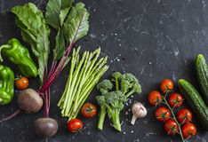 新鲜的季节性菜-甜菜根,芦笋,硬花甘蓝,蕃茄,胡椒,在黑暗的背景的黄瓜 健康概念的食物 免版税库存图片