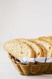 新鲜的家制面包片断在一块白色毛巾的在篮子 库存照片
