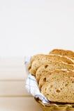 新鲜的家制面包片断在一块白色毛巾的在篮子 免版税库存照片