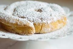 新鲜的家庭焙制的传统西班牙和菲律宾卷起的甜面包ensaimada洒与在蛋糕立场的糖粉 库存图片