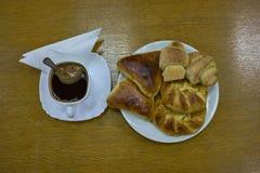 新鲜的小圆面包和小馅饼在一块板材有咖啡盖帽的  免版税库存照片