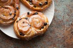 新鲜的小圆面包用葡萄干和结冰在老生锈的背景 与拷贝空间的顶视图 图库摄影