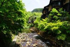 新鲜的小河看法与石银行的通过绿色树和地点 免版税库存照片