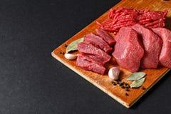新鲜的屠户切开了在黑背景的肉分类 免版税库存照片