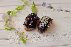 新鲜的巧克力饼在与绿色词根和花的白色鞋带餐巾放置 库存图片