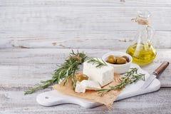 新鲜的希腊白软干酪用在白色木服务板的迷迭香 免版税库存照片