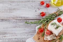 新鲜的希腊白软干酪用在白色木服务板的迷迭香 免版税库存图片